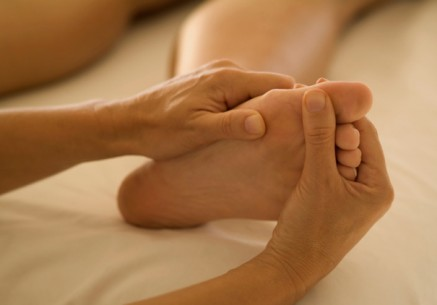Person receiving foot massage, close-up, part of
